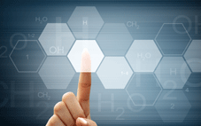 finger touching a screen with a network of chemical formulas