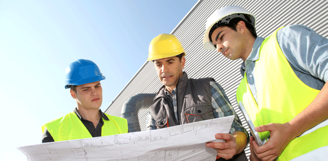 utility workers reviewing blueprints