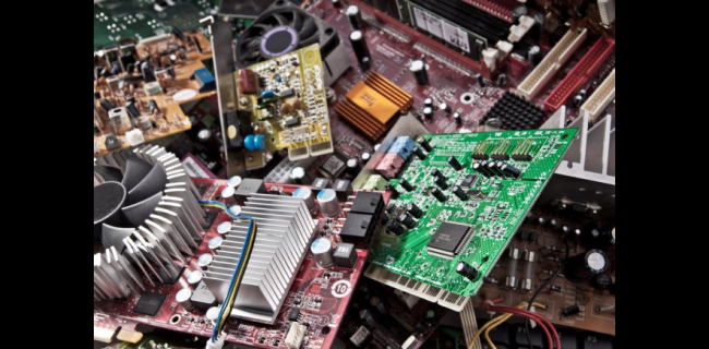 A collection of used computer motherboards and graphics cards.